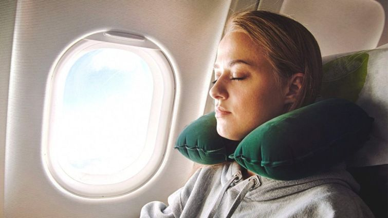 a person sleeping in the window seat of a plane